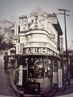 Post-war photo of Nagasaki, Japan by Tadahiko Hayashi. This cigarette & souvenir shop standing at the bottom of the hill coming down from Ōura Tenshudō still runs as of today, it seems.  *Ōura Tenshudō, or the Ōura Church is a Roman Catholic church built in 1864 promoted by two French missionaries who landed in Nagasaki for the purpose, which is said to be the oldest Catholic church in Japan…