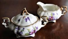 This is a beautifully crafted cream and sugar set -- even more sweet because it is in miniature size. The sugar bowl is covered, making this a 3-piece set. The white china background sets off a beautifully painted scene of purple violets and green leaves and vines. There is quite a lot of rich gold accent on the handles and lid, on the feet of each item, and around the rims. Overall this 3-piece violet-patterned cream and sugar set is in excellent vintage condition with only a little wear on…