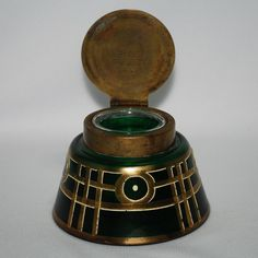 "Bohemian-Czech Glass Inkwell with Gold and Enameled Decoration - emerald green inkwell was made in the early 1900s. It features a soft satin surface on the glass, and an interesting geometric Jugendstil design painted with gold and white enamel. The brass lid is stamped underneath with ""Oe Patent Hansa DRP D.R.G.M."". We are unsure who the maker of the glass inkwell was. The glass insert is a replacement and is almost a perfect fit."