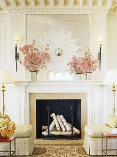 Mantle styling.  Blossoming branches + white sunburst mirror | Suzanne Tucker