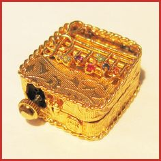 This is a tiny Swiss made music box pendant that plays a sweet little tune and has a hidden message as well. The musical notes in the decoration are studded with seven precious gemstones. The first letters of the gemstones spell out DEAREST ... Diamond, Emerald, Amethyst, Ruby, Emerald, Sapphire, Topaz. This little acrostic was popular in late Victorian jewelry. The box itself is crafted of 14k gold and the tiny musical movement is made by Colibri, one of the finest Swiss makers.
