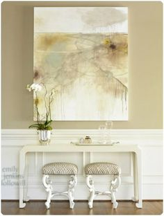 Taupe walls are anything but boring when partnered with crisp white wainscoting, large scale art, and fabulous home accents like those perfect stools tucked underneath a modern curved console.