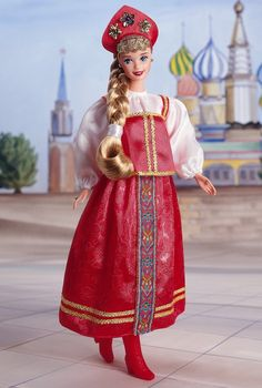 Welcome Russian Barbie doll, in her authentic costume that could be worn during a traditional festival or wedding. She has a red tunic trimmed with golden braid and worn over a white blouse. Her skirt is also trimmed with a multicolored braid down the center and a golden braid around the hem. Her red and golden hairpiece crowns her blonde hair, which is worn in a long, thick braid. To fully authenticate the look, she wears red boots and golden earrings.