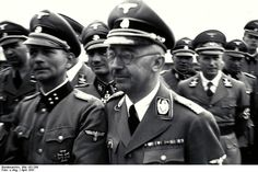 "Heinrich Himmler visits the Mauthausen concentration camp in April 1941. Obsessed with ""efficiency"" of the killing business, Himmler was interested in every minute detail during such visits. Always surrounded by a throng of SS officers, he insisted on getting an answer immediately -- and thus every commandant would mobilize his entire staff for a Himmler visit. The apotheosis of organized mass murder."