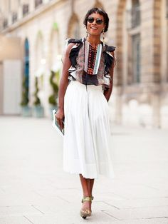 www.poshmap.com Long pendant earrings are worn with a patterned sleeveless top and a white midi skirt.