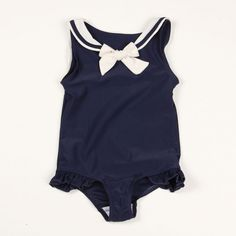 SAILOR SWIMSUIT DK. BLUE MINI RODINI Gorgeous swimsuit with sailor collar and bow at chest. The colours are in classic combination of white and navy for a maritime chic look. It has a cute frill at leg opening and is lined with mesh.