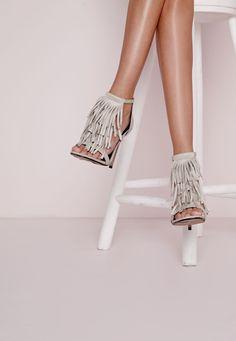 Cette saison, préparez-vous à faire des émules dans ces sandales à talon grises. On craque complètement pour ces chaussures en faux daim qui présentent des franges à l'avant et une fermeture éclair à l'arrière. Avec leur coussinet...
