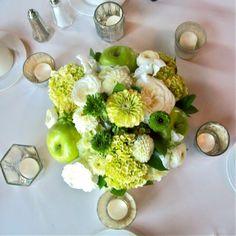 Apple Green centerpiece with green zinnia, green ranunculus, white garden roses, green mini hydrangea, apples and mercury glass votive candles for Michigan Wedding