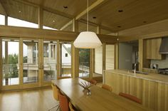 """Boora Architects have designed a modern residence, located on the bay side of a peninsula on the Oregon Coast, USA. The project has a total area of 2,865 square feet and was developed in a """"U""""-shape, around a central courtyard. Its design captures the surrounding views and was associated by the architects with a glowing lantern in the marshland, during night time."""