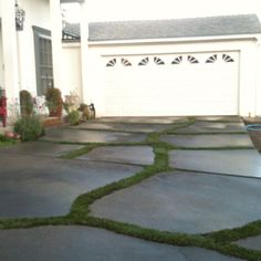 We fixed our old cracked driveway by widening the cracks, staining the cement and planting sod in the cracks:)