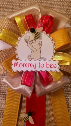 """A baby shower corsage is a way you can express how rewarded you feel to become a mom, time and time again.   Classic Winnie the Pooh Inspired Baby Shower Corsage Pin   Mommy to bee - approx. 4""""Wide by 10""""Long  - Honey yellow, yellow, beige, burlap, red."""