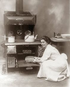 This picture shows a woman cooking in an old wood stove. The picture was taken in 1909. It looks like she is baking bread.