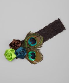 Look no further for a mini maven's new statement piece. With shimmering peacock feathers and a trio of satin rosettes, this headband is positively glamorous and girly, while stretchy lace keeps the fit comfy.