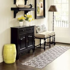 LOVE the COLORS - cream beaded board wallsm wood floors, black side table and mirror and bench, floor lamp.