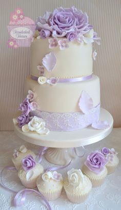 Ivory wedding cake with giant lilac roses and matching cupcakes www.homebakedheaven.co.uk