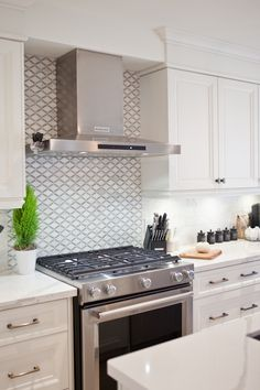 I chose this beautiful basketweave tile as a centerpiece and focal point behind the stove. We framed it out with marble pencil, added marble tile in a brick style pattern and used a warm grey grout to accent it which pulls together the grey from the backsplash and countertop. I love the way it turned out, and created an eye catching vignette in the heart of the kitchen.
