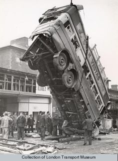 An unusual view of bomb-damaged LT-type bus, LT669, which has just been lifted from the bomb crater in Balham into which it had fallen on the night of 14 October 1940. It can be seen that the roof of the bus is missing, and all the windows have been smashed. A group of workmen are standing on the road, watching the operation. Note the damaged building on the left.  Photographed by Topical Press, 30 Oct 1940  Location: Wandsworth SW17