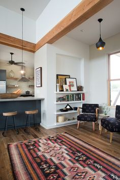Colourful rug, built in bookshelves, exposed beams