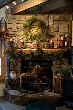 A rustic, warmly decorated fireplace with simply draped greenery, vintage/antique Santas and an antique rocking horse on the hearth stone.. .