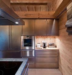 Rostfreier Stahl, Stein und Holz treffen in der Hütte Küche