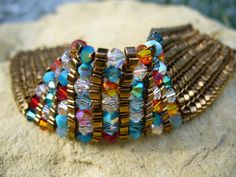 close up of bracelet with multi colored crystals and bronze beads.