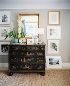 Black and gold chinoiserie dresser vignette - gold mirror - orchid in turquoise pot - Lonny Mag