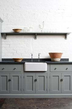 Grey-green painted cabinets with black soapstone, white farmhouse sink