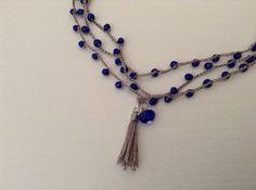 Collana a uncinetto realizzata a mano, catenella con filo di seta di colore grigio e perline blu, ciondolo composto da una nappina grigia e pietra swarovski blu. Collana lunga da - 15456129