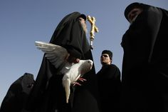 A Greek Orthodox priest holds a dove before a ceremony at the baptismal site known as Qasr el-Yahud on the banks of the Jordan River near the West Bank city of Jericho. By Baz Ratner