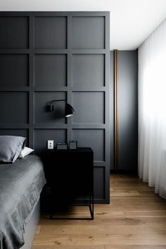 moody dark grey bedroom with square wall panels | modern minimal bedroom decor | industrial style bedside table and wall sconce | white curtains let light through | wooden floors | Nail the all grey trend with a Bemz bedspread in Graphite Grey Chenille