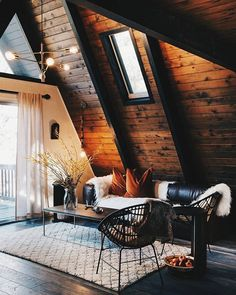 A A-Frame Cabin in Big Bear Is Brought Back to Life - Photo 4 of 12 - Picks from West Elm furnish much of the living space, including the chandelier, coffee table, and rug. A leather Article sofa sits next to a pendant light from Anthropologie.
