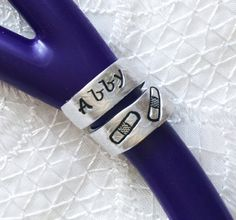 FLOWER PATTERNED WRAP STETHOSCOPE ID RING/TAG  This design came from a request of a student nurse. She needed the ID ring but isnt a full registered nurse yet. We created something just perfect for that problem. It doesnt have the RN title, but it still has the name and a cute personal touch to it. It is a floral pattern texture that is done to the metal before the lettering is set onto the ring. I have tried to zoom in very closely so you can see the pattern on the ring for picture #3. ...