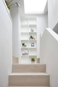 Up the stairs, with natural light coming from the skylight above. To the left is the kitchen.