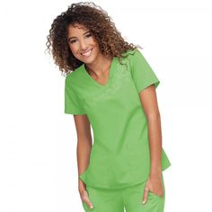 Orange Standard Malibu Top in Appletini. This mock wrap ladies scrub top comes in a variety of fresh, bright colours. The Orange Standard Malibu Top has a stylish Y neckline with beautiful floral detail, side slits for easy fitting and two practical pockets. This scrub top looks fantastic with Orange Standard Laguna Trousers and is made from 65% Polyester and 35% cotton.£19.99  #nursescrubs #dentistuniform #nurses #dentists #greenscrubs