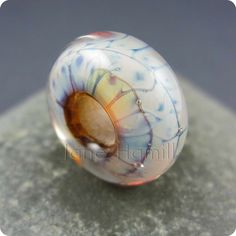 """The base of this bead is a pale brown or amber clear glass; when I applied the silver-rich glass on top of it, the glass became a pale, almost pearlescent colour which reflect light through the core and makes it appear to have a golden glow, hence the name """"Golden Dragonskin"""".  ➻ Effetre and Double Helix glass. ➻ Diameter: 18.5mm ➻ Depth: 8.5mm ➻ Hole size: 5.4mm"""
