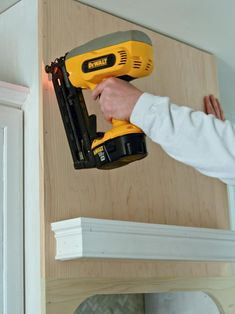 To attach a front panel for a custom range hood project, fit the front panel onto range hood and nail in place with finishing nailer.