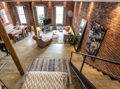 This historic Seaport home has a spacious dining/living space with exposed brick walls, wood center beam and column, gray tufted furniture, a long dining room table, long gray curtains and lofted bedroom. Industrial Home Design, Industrial Bedroom, Industrial House, Small Space Living, Small Spaces, Long Dining Room Tables, Nyc Real Estate, Exposed Brick Walls, Tiny House Design