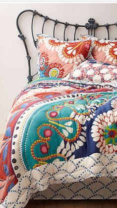 Love the Art Nouveau headboard and the colourful spread.