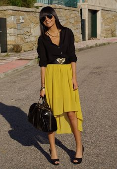 Yellow high and low skirt with a black sheer top and an elephant belt. Adorable