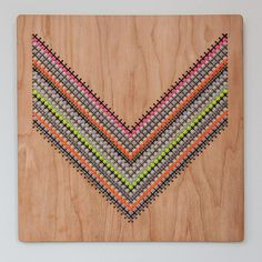 Modern, geometric pattern cross stitched into laser cut 12 inch by 12 inch birch wood panel. This design features a chevron pattern in various shades