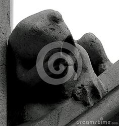 Shot in black and white, detail on an sculpture representing a strange creature placed at the facade of this historic building, set in Eixample, Barcelona, Catalunya, Catalonia, España, Spain, Europa, Europe