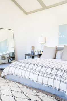 Minimal bedroom wiht a slipcovered linen bed, an oversize mirror, and a mayan throw