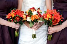 Rose And Berry Bouquets: These rose and gerbera daisy bouquets are perfect for traditional brides that want an impactful pop of color against the bridal party's dresses. Make the bride's bouquet unique from the others by including a few cream roses.