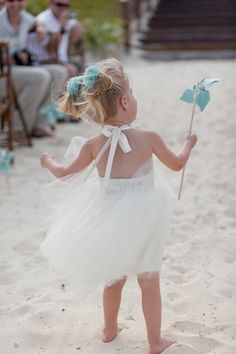 Pom pom scrunchies and a pinwheel at this #beachwedding - too cute! #flowergirlinspo
