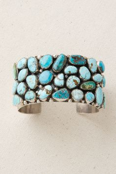 This is a large, wide, substantial cuff bracelet made with 28 bezel set turquoise stones. Many different types of turquoise of various hues combine to make this a very versatile bracelet. The colors range from light blue to deep green. The turquoise stones are accented by handmade sterling silver beads and the background is heavily …