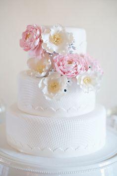 Add flowers to an elegant white cake.