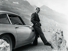 James Bond (Sean Connery) and his iconic Aston Martin DB5, filming Goldfinger (1964) at the Furka Pass, Switzerland. GOLDFINGER © 1964 Danjaq, LLC and United Artists Corporation. All rights reserved.   - Esquire.com