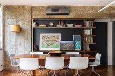 Decoração de apartamento com concreto na sala de jantar cadeiras brancas, mesa de madeira, quadros, adornos.