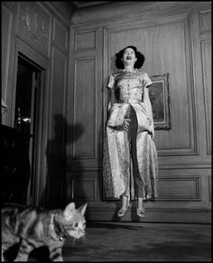 0 kitty carlisle jumping in the air while her cat walks by 1958 by philippe halsman
