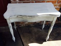 "This is an interesting little table. I think it was a card table at one point, the top swivels and opens up to reveal a hidden compartment and it also opens up the table to be bigger. I painted it a distressed white.   It would work great as an entry table or a sofa or accent table.  The dimensions are 34"" L, 17"" W, 31"" H folded up and 34"" L, 32"" W, 31"" H unfolded.. Sold for $80"